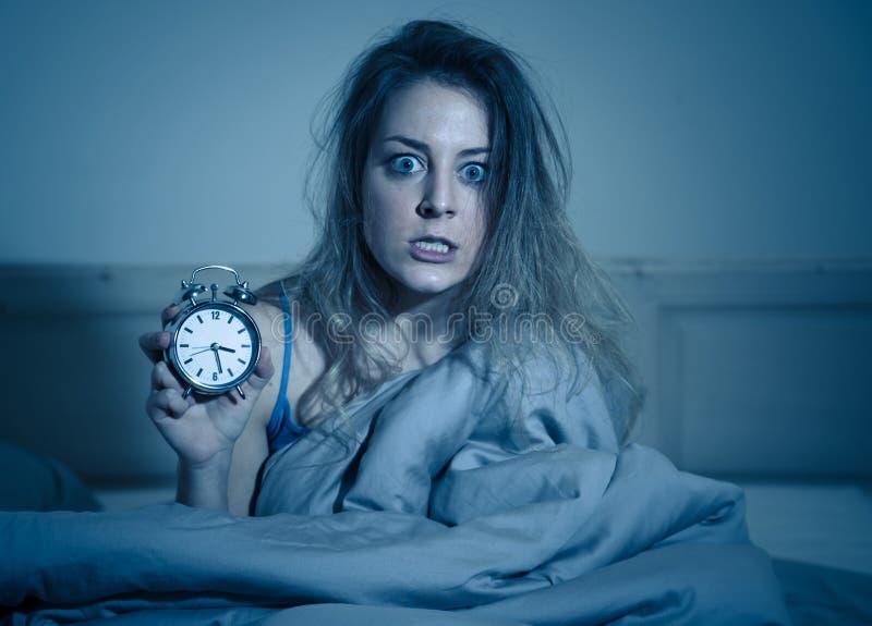 Mulher atrativa no despertador da exibição da cama ao sentimento da câmera preocupado, forçado e sem sono imagem de stock royalty free