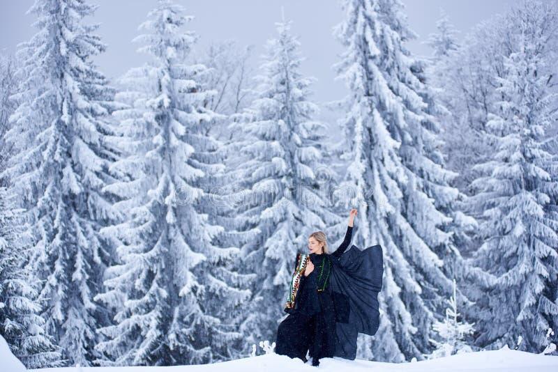Mulher atrativa no equipamento longo escuro da fantasia fora na neve profunda no dia de inverno ensolarado foto de stock royalty free