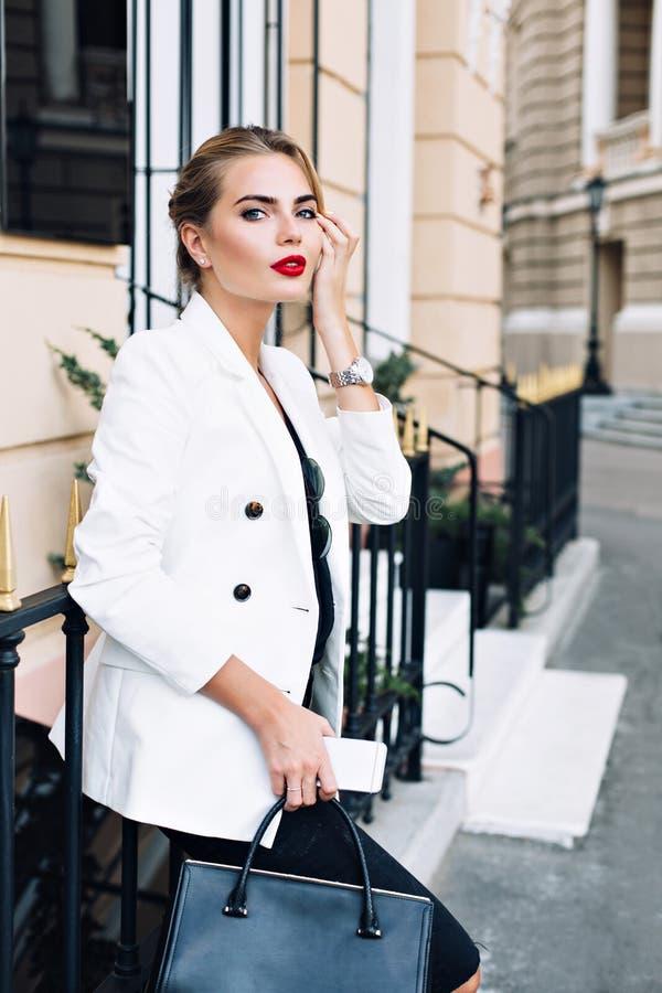 A mulher atrativa no revestimento branco está inclinando-se na cerca na rua Tem os bordos vermelhos, olhando à câmera imagem de stock royalty free