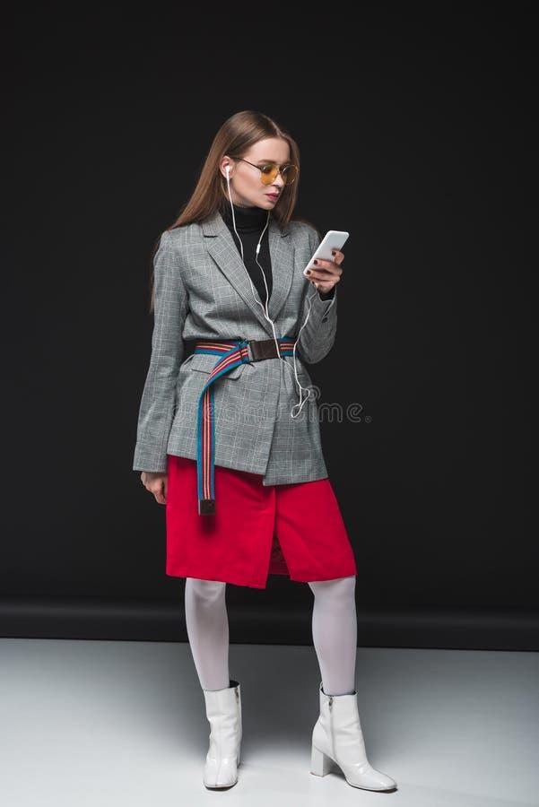 Mulher atrativa no revestimento cinzento e na saia vermelha que escuta a música imagens de stock royalty free
