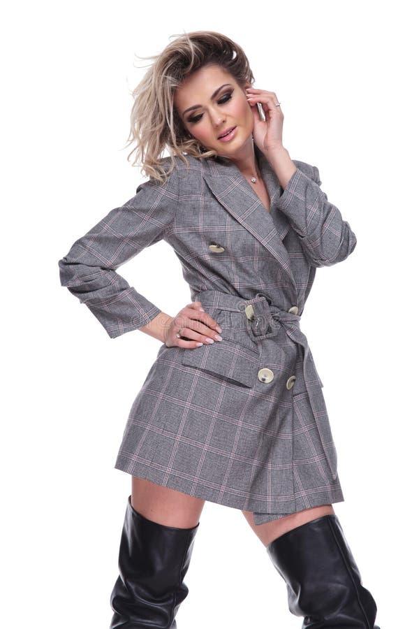 A mulher atrativa no terno cinzento e nas botas de couro olha para baixo fotos de stock royalty free