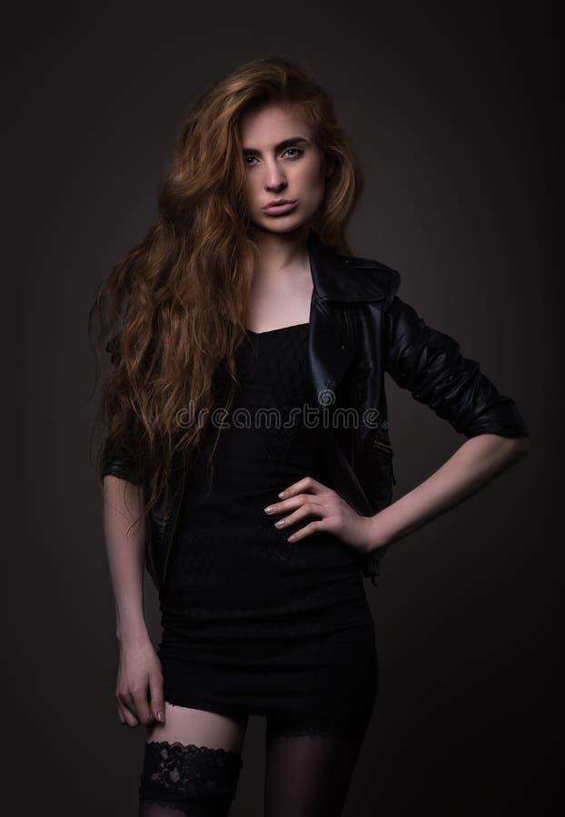 Mulher atrativa no vestido e no casaco de cabedal pretos fotos de stock royalty free