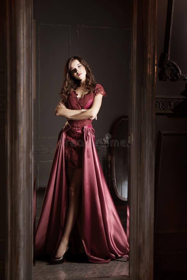 Mulher atrativa no vestido longo do laço do clarete Refletido no espelho imagem de stock royalty free