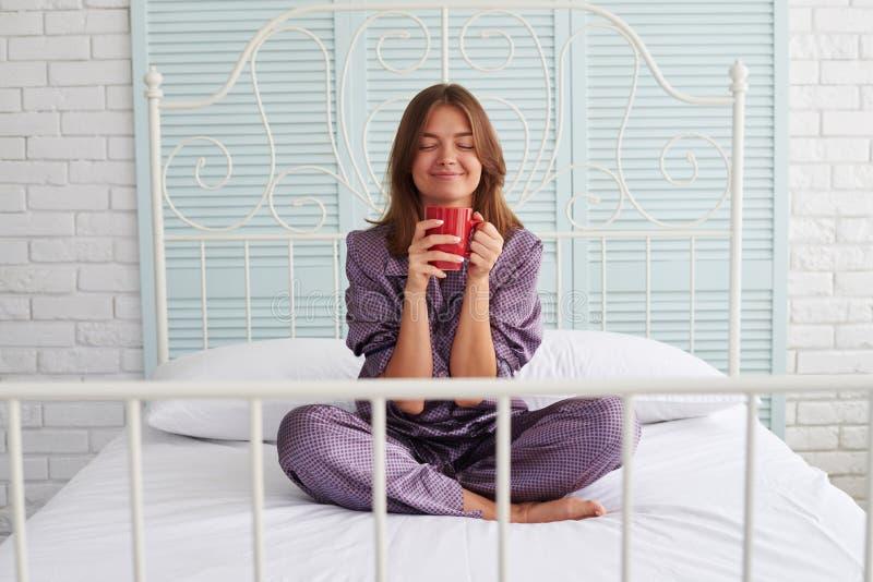 Mulher atrativa nos pijamas na cama que aprecia o cheiro de sua ANSR foto de stock