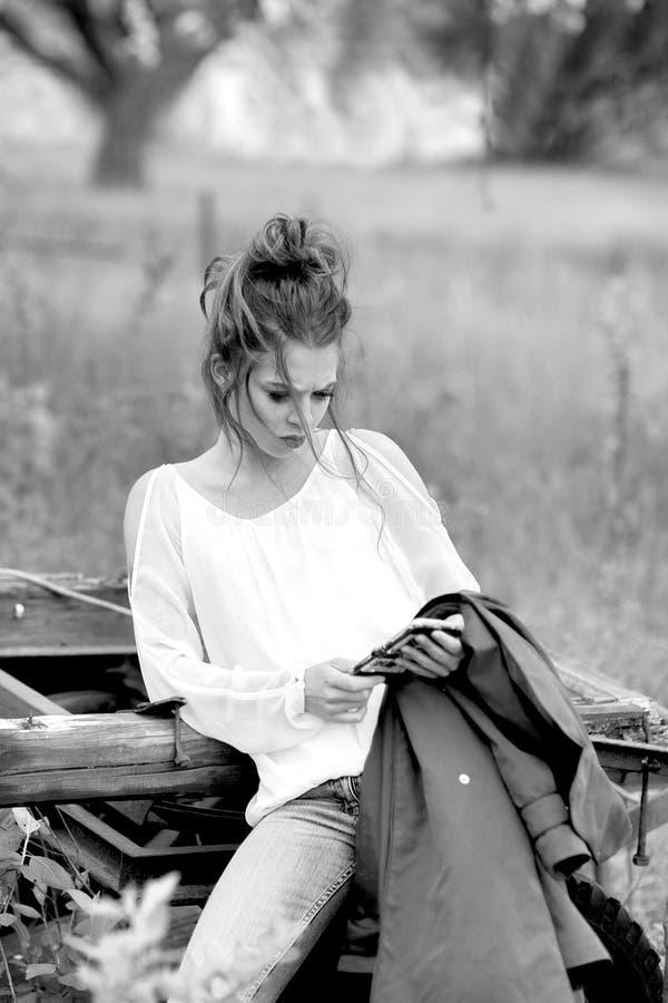 A mulher atrativa nova é ocupada com seu telefone celular que faz selfies, escrita, leitura fotografia de stock