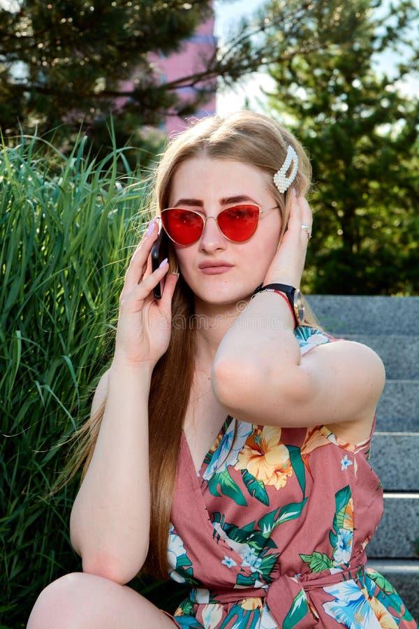 Mulher atrativa nova Óculos de sol vermelhos, vestido da cor, telefone celular, 5G, 4G, 3G, 2G, rede de LTE foto de stock royalty free
