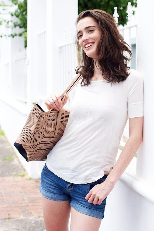 Mulher atrativa nova com bolsa e inclinação contra a cerca foto de stock