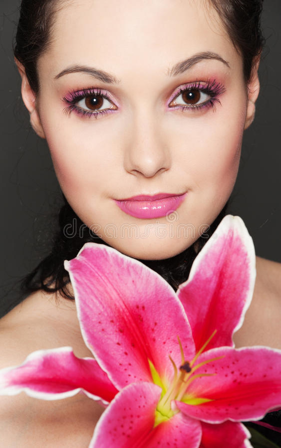 Mulher atrativa nova com lírio cor-de-rosa imagens de stock royalty free