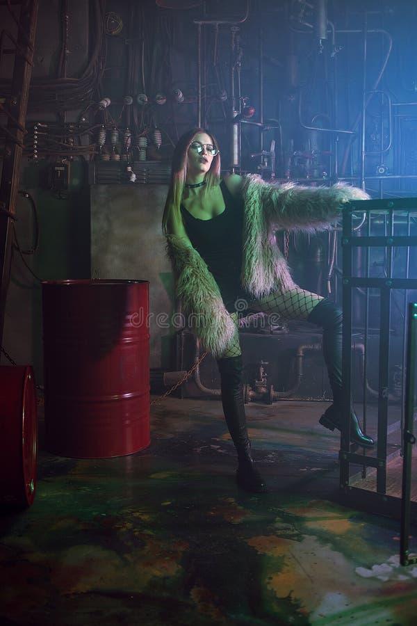 Mulher atrativa nova com roupa à moda Menina bonita no casaco de pele cor-de-rosa macio, fundo do Cyberpunk Luz de néon foto de stock royalty free