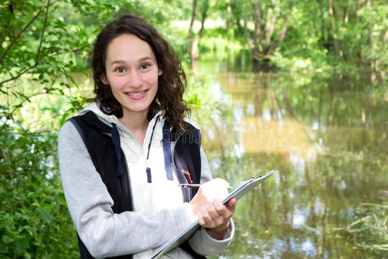 Mulher atrativa nova do biólogo que trabalha na análise de água imagens de stock