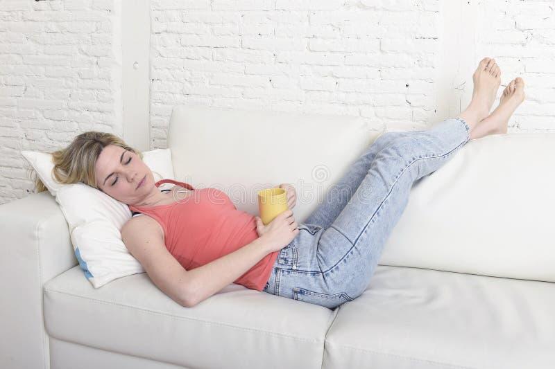 Mulher atrativa nova do cabelo louro que mantém a xícara de café que encontra-se no sono da sala de visitas do sofá do sofá em ca fotografia de stock