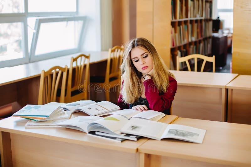 Mulher atrativa nova do estudante que senta-se na mesa em livros de estudo velhos da biblioteca da universidade e preparação para imagens de stock royalty free