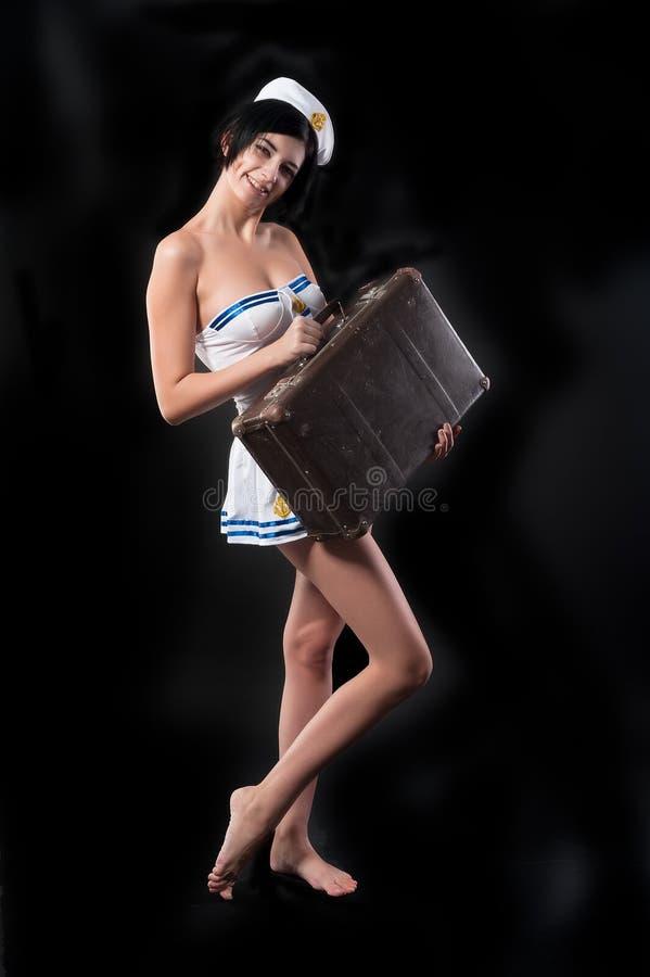 A mulher atrativa nova do marinheiro sorri com mala de viagem foto de stock royalty free