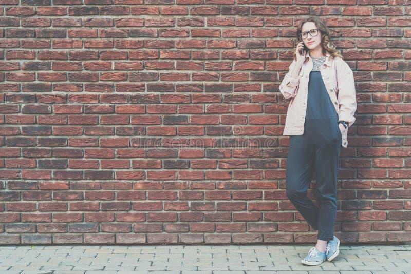 A mulher atrativa nova do moderno está fora em um fundo da parede de tijolo vermelho e fala em seu telefone celular fotos de stock royalty free