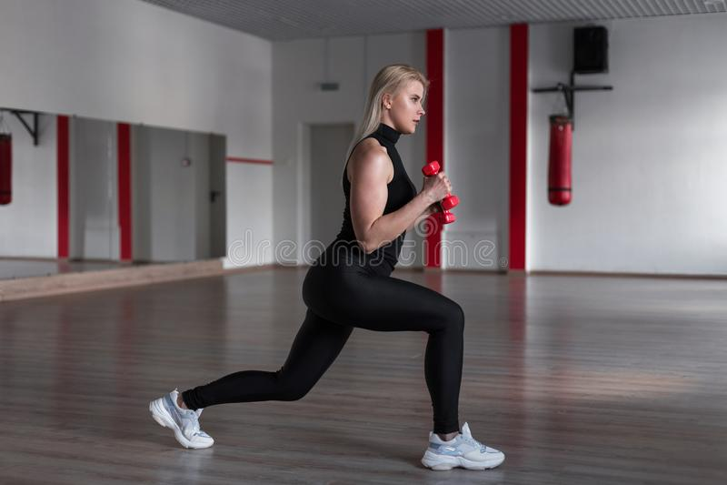 Mulher atrativa nova em caneleiras pretas no t-shirt dos esportes que faz exercícios com pesos nas mãos no gym imagem de stock