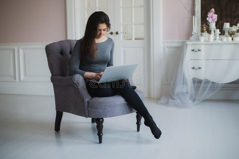 Mulher atrativa nova em casa, trabalhando com portátil, classes em linha livres para o interesse, começar caseiro da mamã imagem de stock