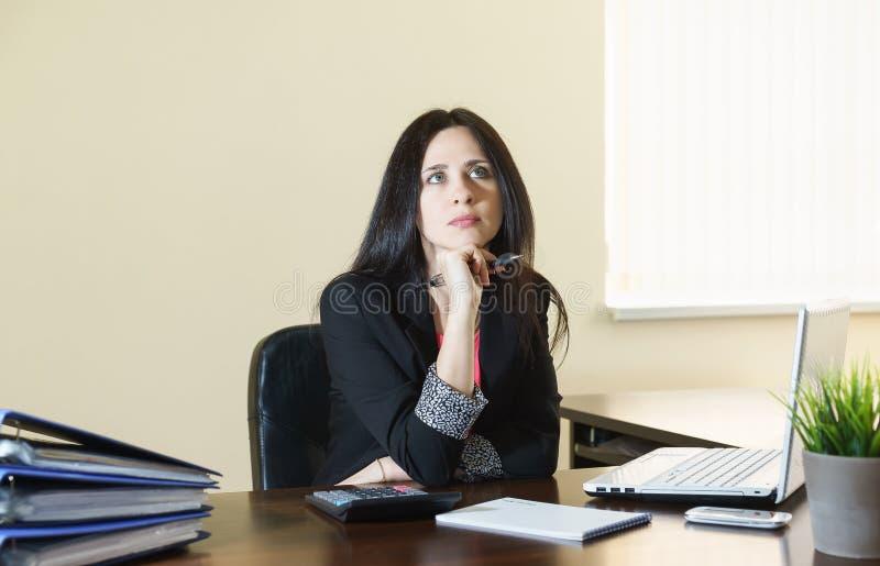 A mulher atrativa nova em um terno de negócio atrás de uma mesa no escritório olha o teto imagens de stock