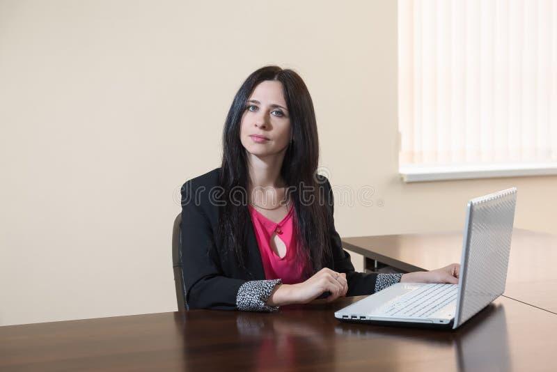 Mulher atrativa nova em um terno de negócio que senta-se na mesa com o portátil no escritório fotos de stock royalty free