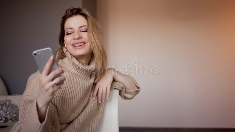 A mulher atrativa nova em uma camiseta senta-se em casa na sala de visitas e usa-se um smartphone foto de stock