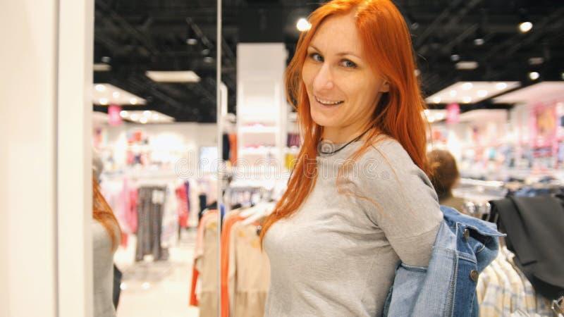 A mulher atrativa nova está escolhendo um revestimento das calças de brim na loja de roupa do ` s das mulheres imagem de stock