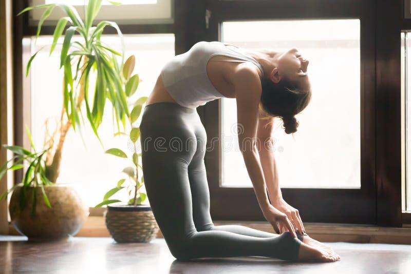 Mulher atrativa nova na pose de Ustrasana, backgrou do interior da casa fotos de stock royalty free