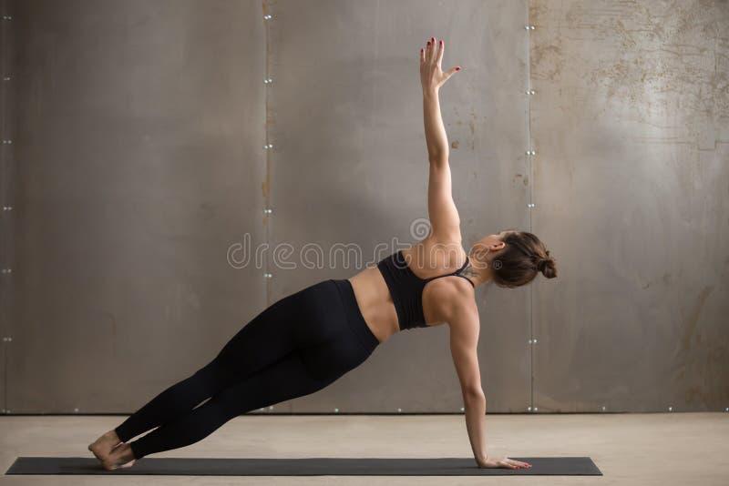 Mulher atrativa nova na pose lateral da prancha, backgroun cinzento do estúdio fotos de stock