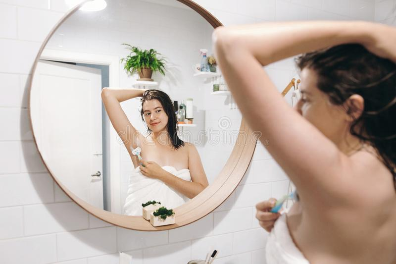Mulher atrativa nova na toalha branca que barbeia as axila, olhando no espelho no banheiro à moda Cuidado da pele e do corpo Remo imagem de stock royalty free