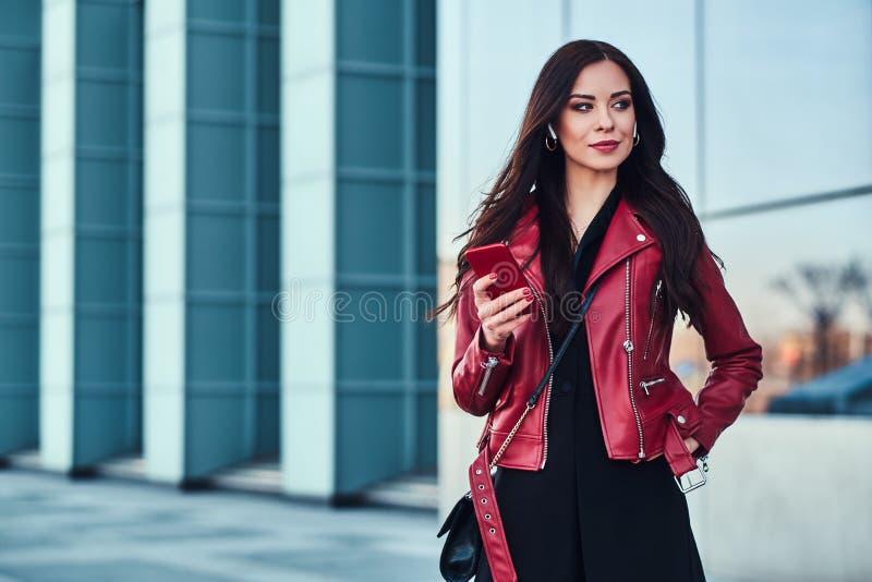 A mulher atrativa nova no revestimento vermelho está apreciando o passeio fora ao esperar alguém com telefone celular nas mãos fotografia de stock