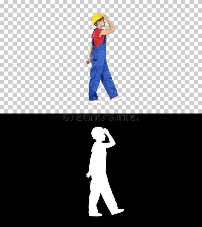 Mulher atrativa nova no uniforme da construção que põe sobre o capacete amarelo, Alpha Channel foto de stock