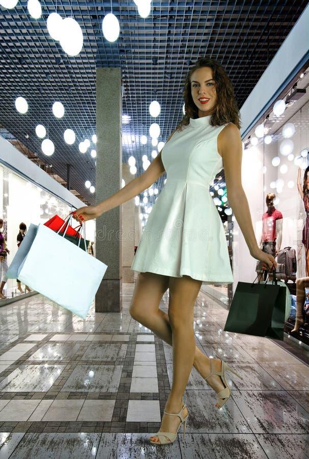 Mulher atrativa nova no vestido branco com sacos de compras fotografia de stock