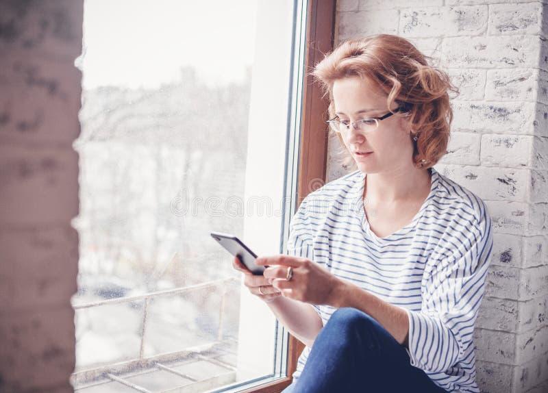 A mulher atrativa nova nos vidros senta-se em uma soleira com A M. fotografia de stock royalty free