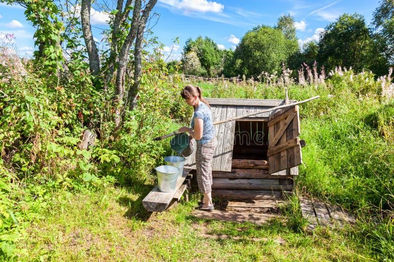 Mulher atrativa nova perto do poço de água de madeira imagem de stock