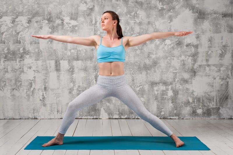Mulher atrativa nova que faz a pose do guerreiro da ioga fotografia de stock