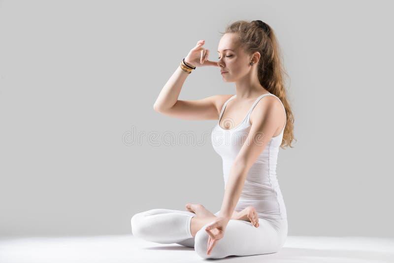 Mulher atrativa nova que faz a respiração alternativa da narina, cinzenta fotos de stock royalty free