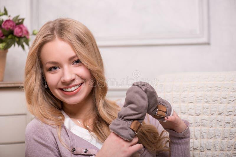 Mulher atrativa nova que guarda mitenes do bebê, imagem de stock royalty free