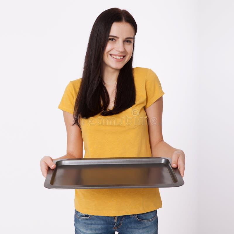 Mulher atrativa nova que guarda uma bandeja vazia no fundo branco foto de stock