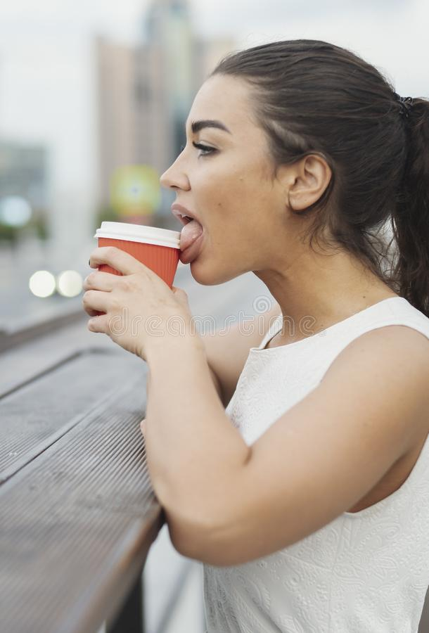 Mulher atrativa nova que lambe o copo de café vermelho fotografia de stock royalty free