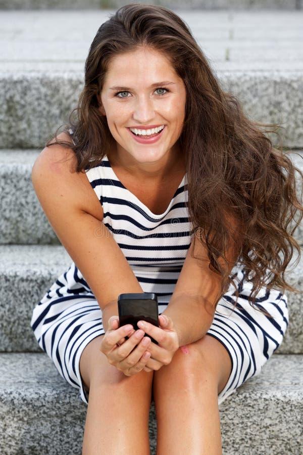 Mulher atrativa nova que senta-se nas escadas que guardam o móbil fotos de stock