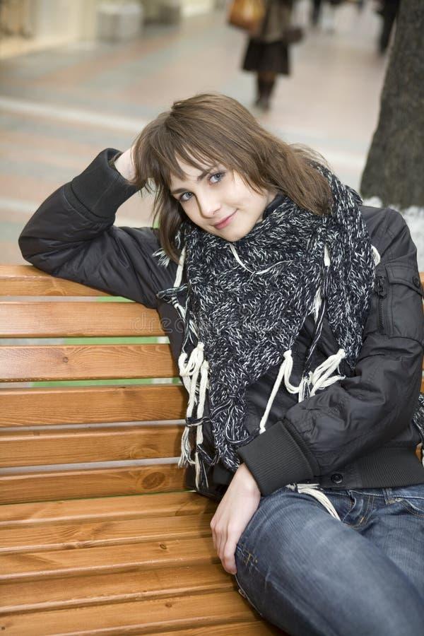 Mulher atrativa nova que senta-se no banco imagens de stock royalty free