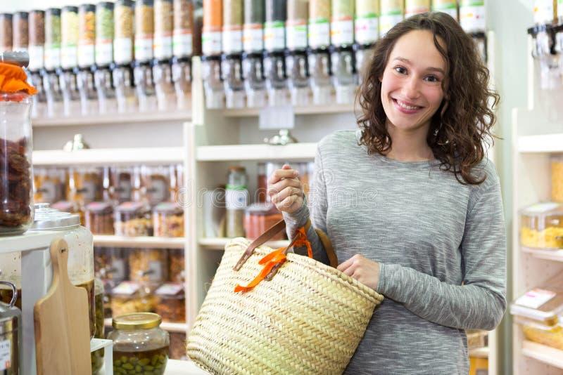 A mulher atrativa nova que shooping afrouxa especiarias no mantimento foto de stock