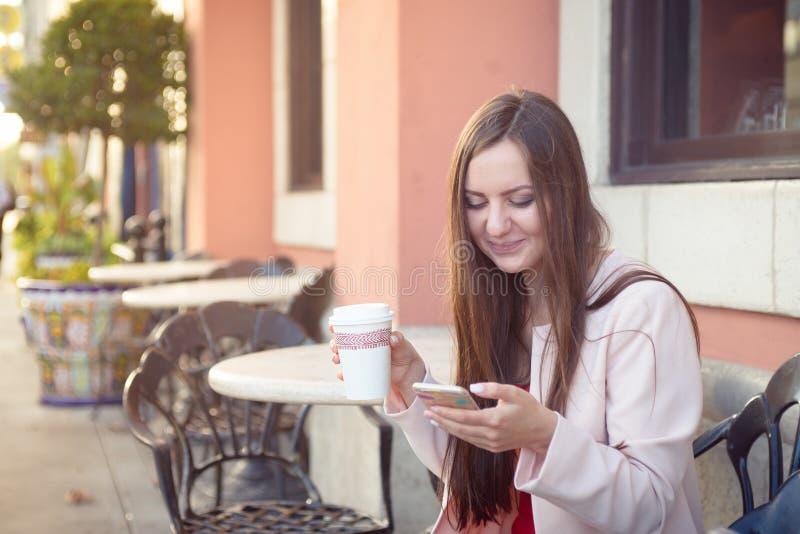 Mulher atrativa nova que sorri com telefone celular e xícara de café fotografia de stock royalty free