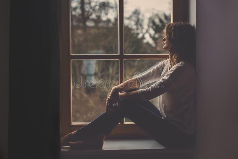 Mulher atrativa nova, sentando-se em uma janela, olhando fora imagem de stock royalty free