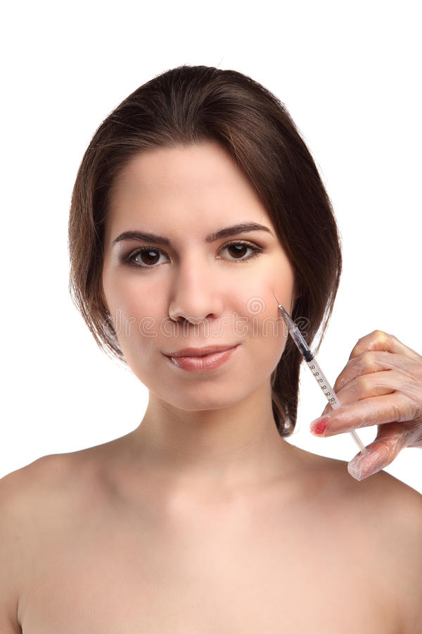 A mulher atrativa obtém a injeção cosmética, isolada sobre o fundo branco Mãos dos doutores que fazem uma injeção na cara foto de stock