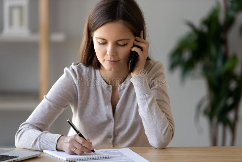 Mulher atrativa ocupada que senta-se na tabela que fala no telefone fotos de stock royalty free