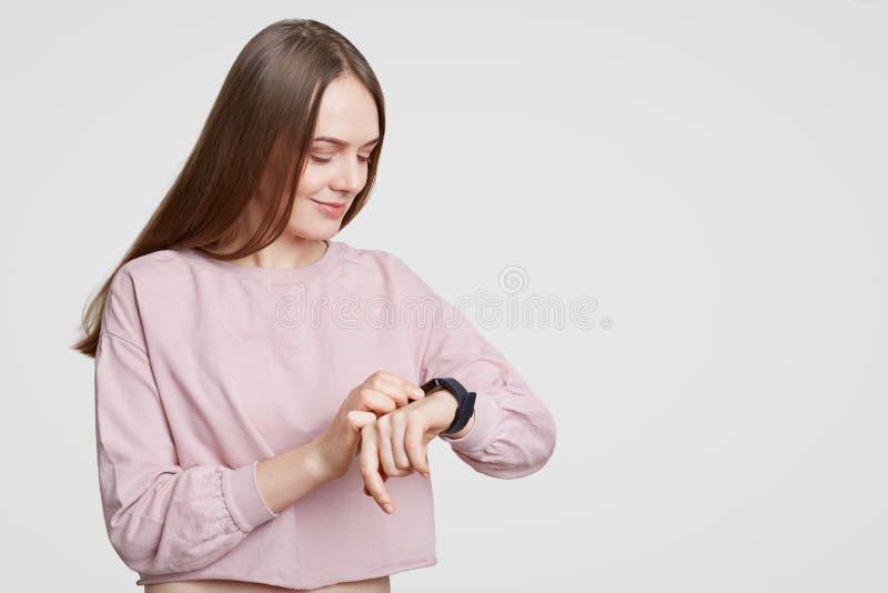 A mulher atrativa olha o smartwatch, verifica calorias ou o pulso, veste a camiseta desproporcionado ocasional, tem o cabelo escu fotos de stock royalty free