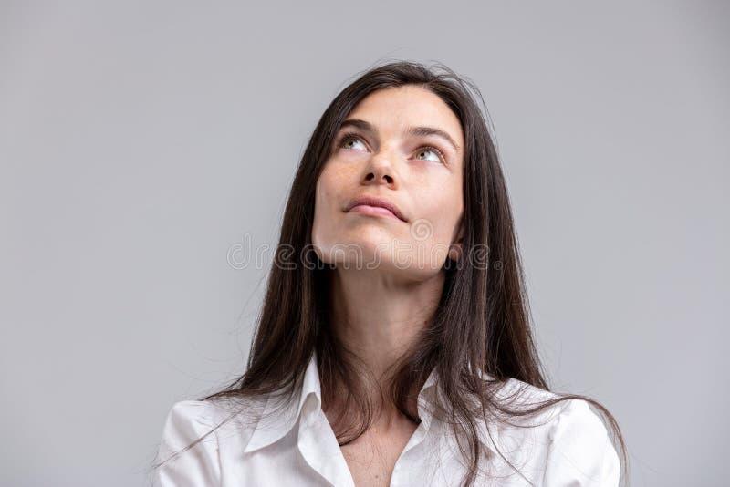 Mulher atrativa pensativa que olha acima fotografia de stock