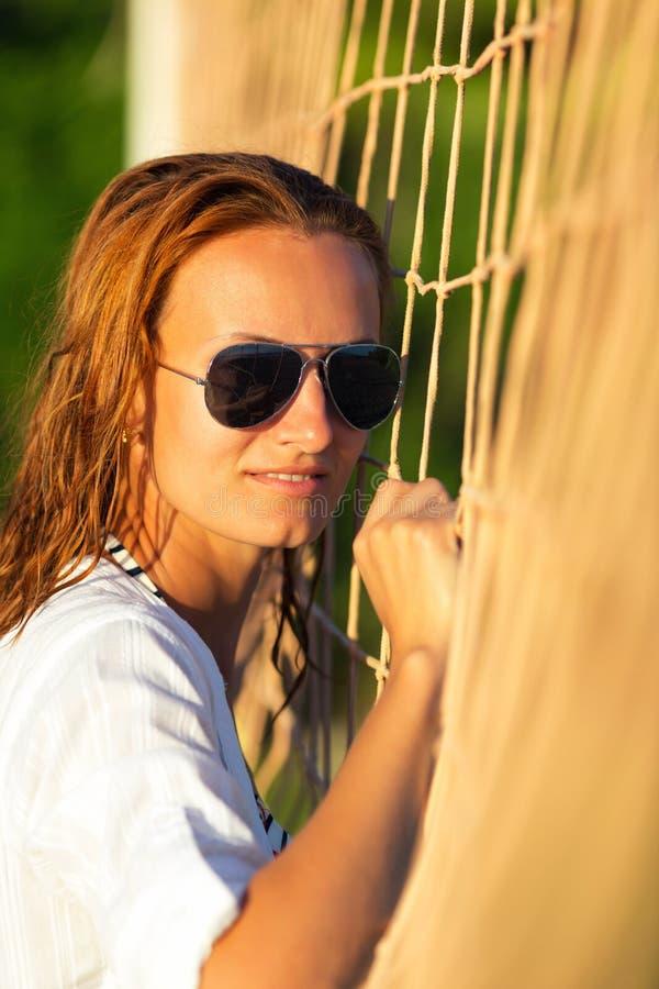 Mulher atrativa perto da rede do voleibol imagens de stock royalty free