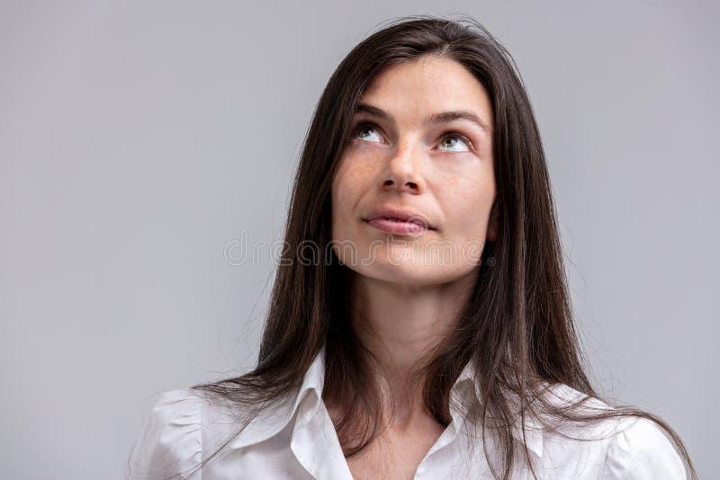 Mulher atrativa profundamente no pensamento que olha acima fotografia de stock