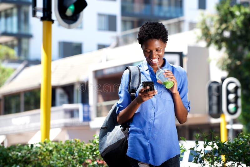 Mulher atrativa que anda na rua usando o telefone celular e bebendo o suco fotos de stock