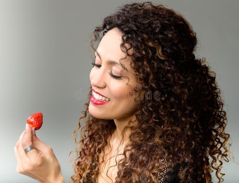 Mulher atrativa que come a morango imagens de stock